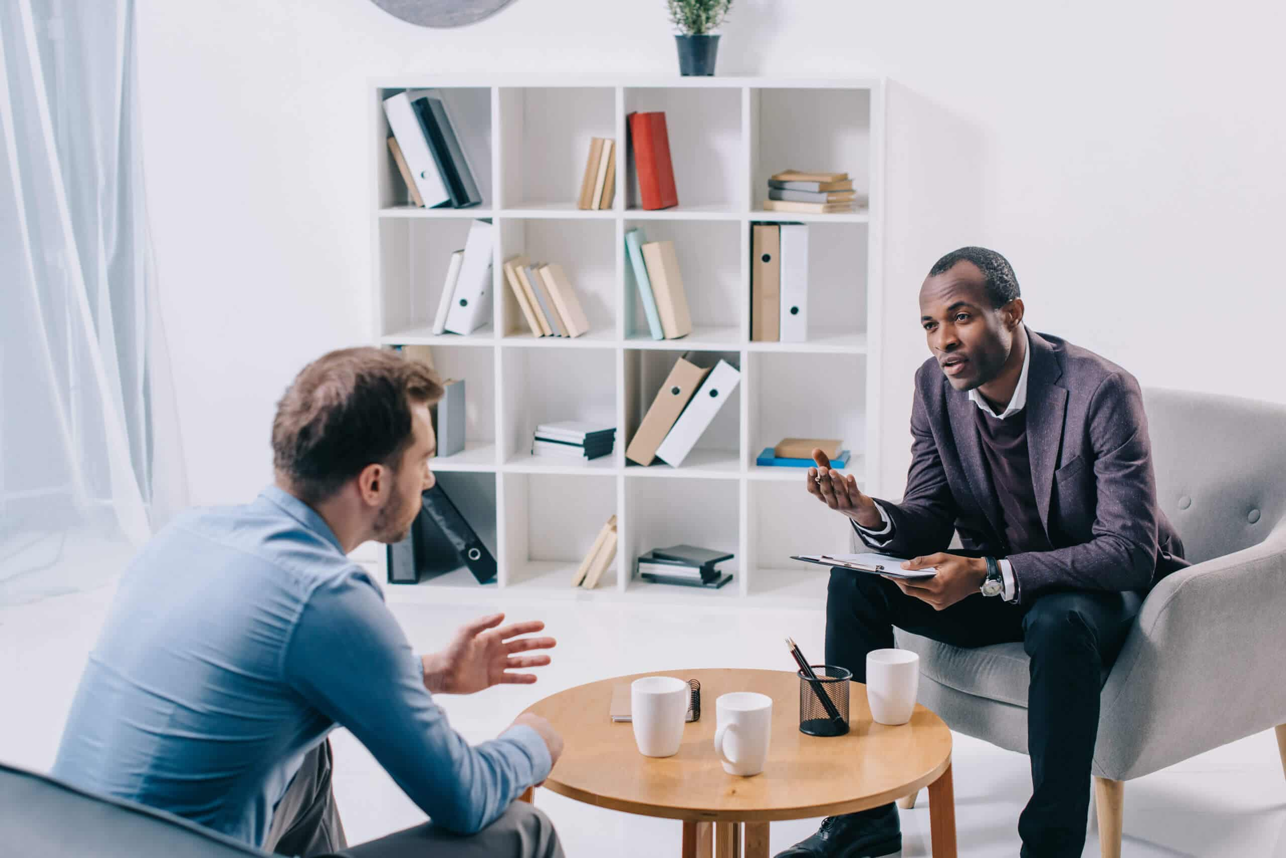 African american psychiatrist talking to young male client